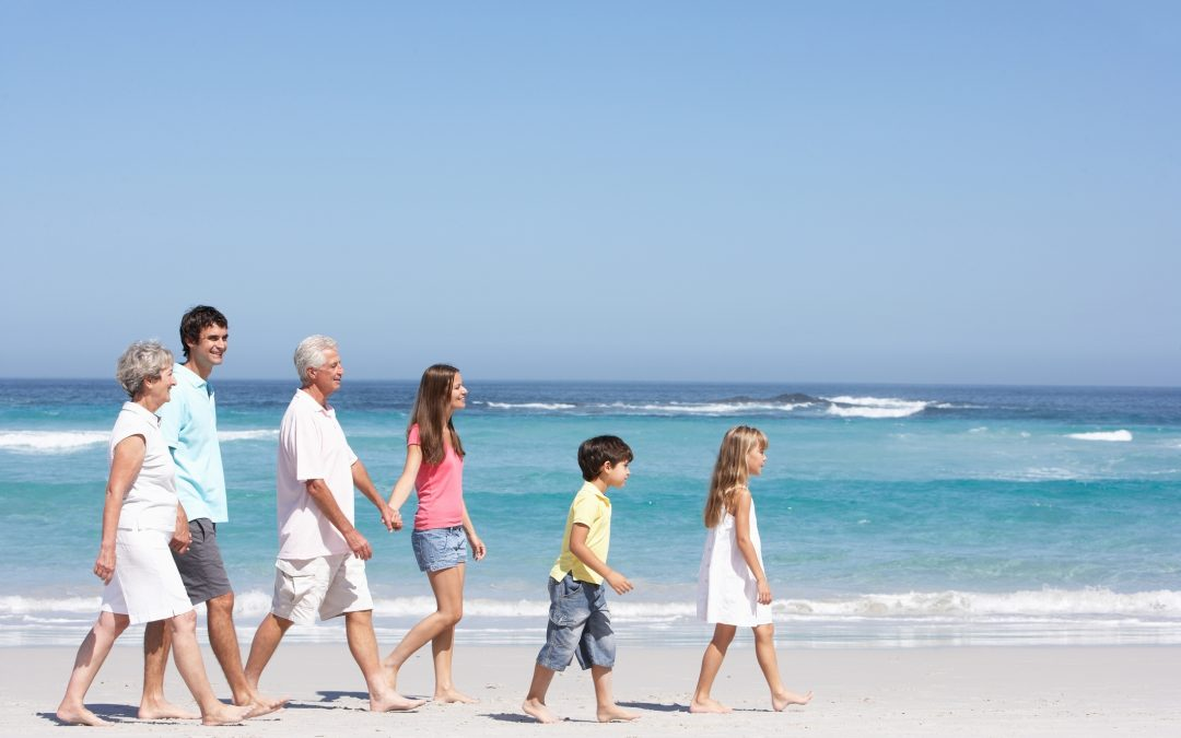 Three generations of a family walk across a beach in the sun
